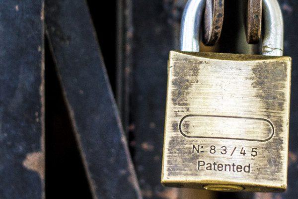 Padlock locked onto black gate
