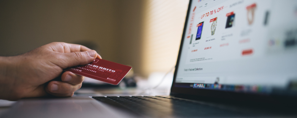 Person holding credit card browsing e-commerce website