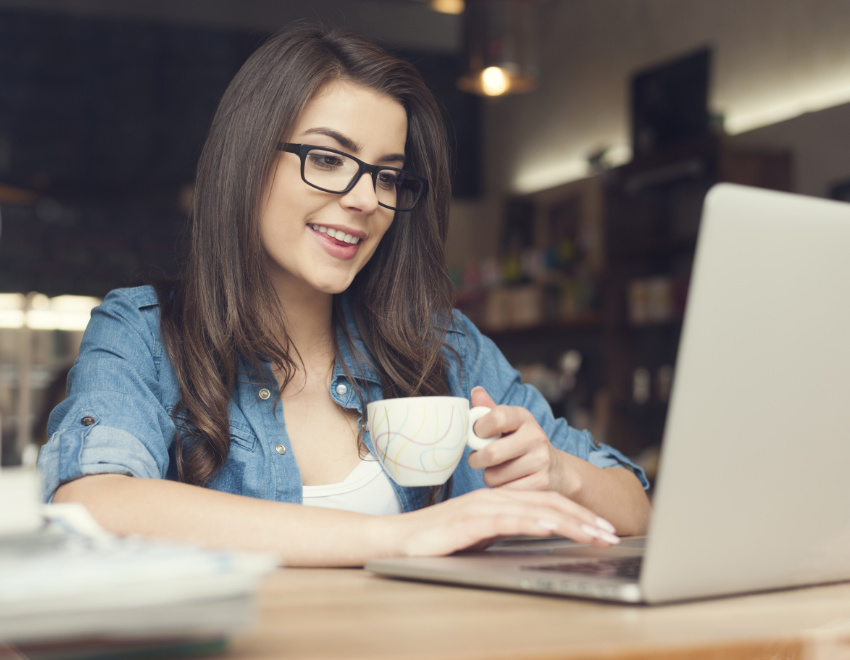 Woman sitting down using laptop checking her email address