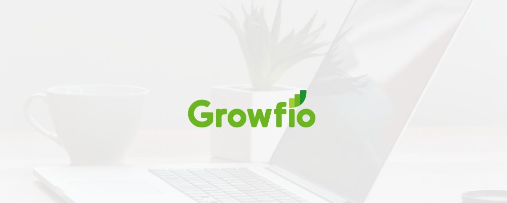 Laptop, phone, plant, and coffe cup on a desk with Growfio's new logo above all